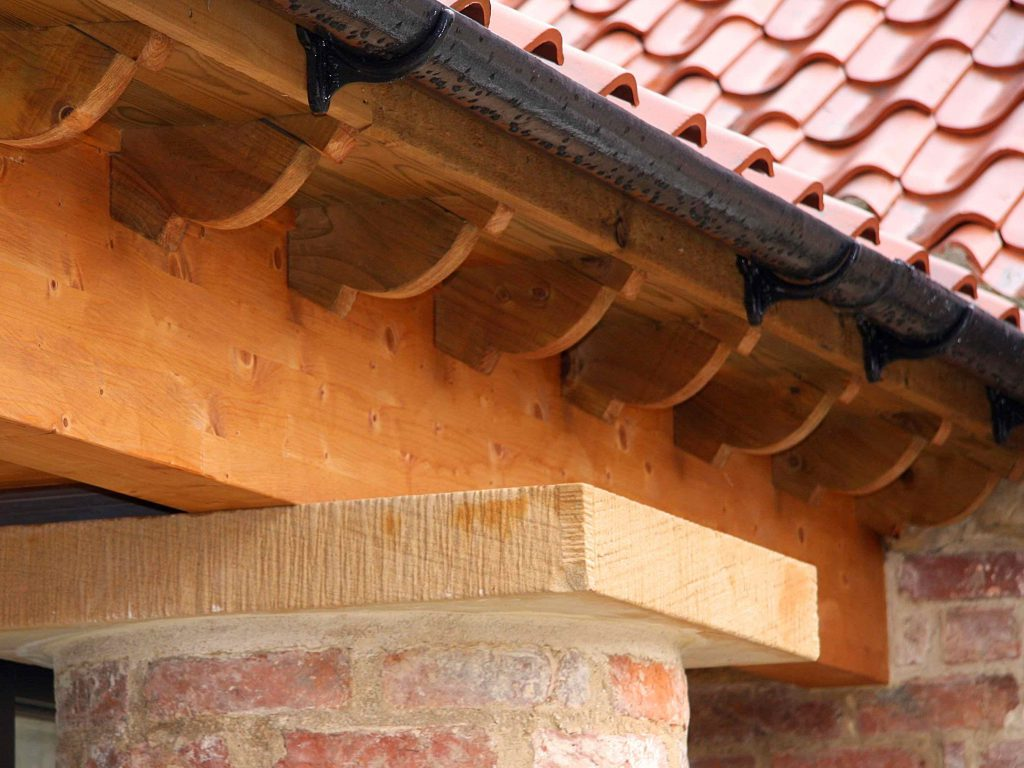 Laminated ring beam with rafter ends to brick columns