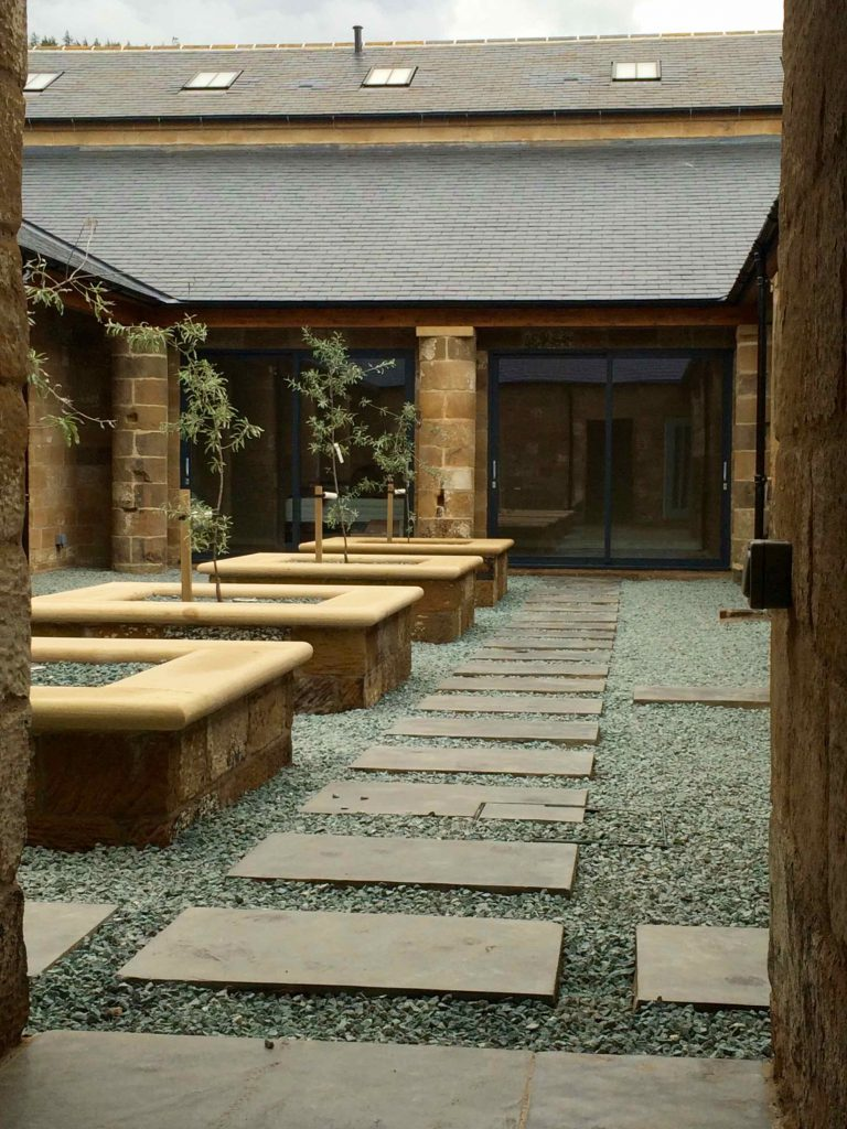 Building matters in an internal courtyard planted with weeping pears